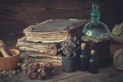 Garrafas da tintura, variedade de ervas saudáveis secadas, livros velhos, almofariz de madeira, saco de ervas medicinais O perfor fotos de stock