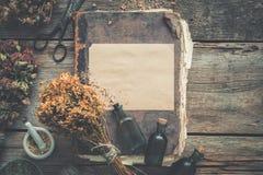 Garrafas da tintura, variedade de ervas saudáveis secas, livros velhos, almofariz, tesouras O perforatum erval de Medicine imagem de stock