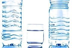 Garrafas de água plásticas com um vidro Fotografia de Stock