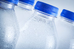 Garrafas de água plásticas molhadas isoladas no fundo branco Foto de Stock Royalty Free