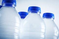 Garrafas de água plásticas molhadas isoladas no fundo branco Fotografia de Stock Royalty Free