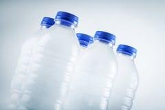 Garrafas de água plásticas molhadas isoladas no fundo branco Fotografia de Stock