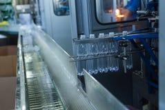 Garrafas de água plásticas na indústria da máquina de engarrafamento do transporte e da água Imagens de Stock