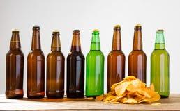 Garrafas de cerveja e microplaquetas de batata em uma tabela de madeira Vista superior Foco seletivo Zombaria acima Copie o espaç imagens de stock royalty free