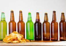 Garrafas de cerveja e microplaquetas de batata em uma tabela de madeira Vista superior Foco seletivo Zombaria acima Copie o espaç fotos de stock