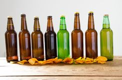 Garrafas de cerveja em uma tabela de madeira Microplaquetas de batata Vista superior Foco seletivo Zombaria acima Copie o espaço  imagem de stock royalty free