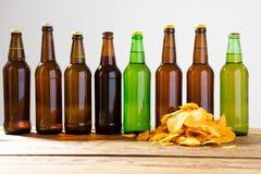 Garrafas de cerveja em uma tabela de madeira Microplaquetas de batata Vista superior Foco seletivo Zombaria acima Copie o espaço  fotos de stock royalty free