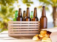 Garrafas de cerveja na caixa de madeira e no bloco de microplaquetas de batata foto de stock royalty free