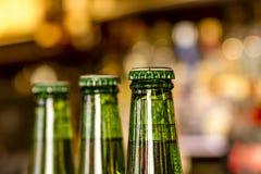 Garrafas de cerveja na frente da barra do Lit Fotografia de Stock