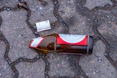 Garrafas de cerveja quebradas no meio do passeio imagens de stock royalty free