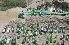 Garrafas de cerveja vazias belamente apresentadas em um pedregulho enorme em um tempo ensolarado fotografia de stock