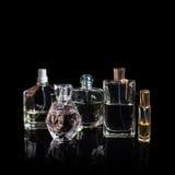 Garrafas de perfume diferentes com reflexões no fundo preto com espaço para o texto Perfumaria, cosméticos, fragrância Imagens de Stock Royalty Free