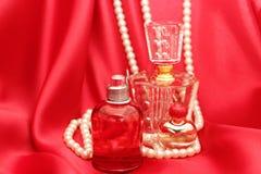Garrafas de perfume e cetim vermelho fotografia de stock