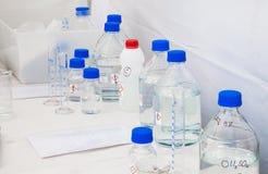 Garrafas de vidro com os tampões azuis com produtos químicos Foto de Stock