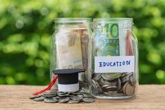 Garrafas de vidro do frasco com completamente das moedas etiquetadas como a educação e a GR Fotografia de Stock