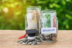 Garrafas de vidro do frasco com completamente das moedas etiquetadas como a educação e a GR Fotos de Stock