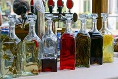 Garrafas de vidro fechados com bebidas coloridas na tabela fotografia de stock royalty free