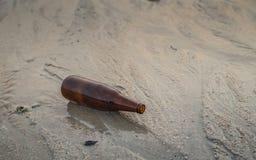 Garrafas de vidro na praia, lixo Fotografia de Stock Royalty Free