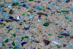 Garrafas de vidro quebradas na areia branca As garrafas são cor verde e azul Lixo na areia Problema ecológico foto de stock royalty free