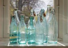 Garrafas de vidro vazias antiquados em uma janela Foto de Stock Royalty Free