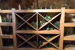 Garrafas de vidro vazias verdes do vinho e da cerveja do vintage em um armário do vinho com prateleiras em uma adega de pedra bri foto de stock royalty free