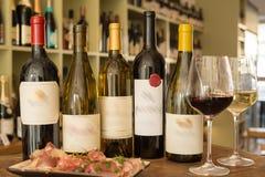 Garrafas de vinho com etiquetas borradas, copos de vinho, e uma placa do supermercado fino Foto de Stock Royalty Free
