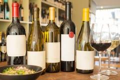 Garrafas de vinho com etiquetas, os copos de vinho, e a bacia vazios de salada Foto de Stock