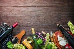 Garrafas de vinho com uvas, queijo, presunto e cortiça Imagem de Stock Royalty Free