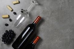 Garrafas de vinho, copo, cortiça e uvas no fundo concreto Copie o espa?o fotos de stock royalty free