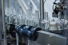 Garrafas de vinho na máquina na fábrica da produção fotografia de stock