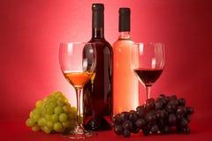 Garrafas de vinho vermelho e branco; uva um vidros bebendo Imagens de Stock Royalty Free