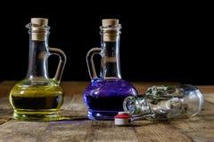 Garrafas do líquido colorido em uma mesa de cozinha de madeira Tabl de madeira Fotografia de Stock Royalty Free