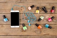Garrafas do verniz para as unhas, do telefone esperto e dos fones de ouvido na tabela de madeira marrom foto de stock