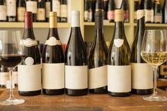 Garrafas do vinho com etiquetas vazias entre copos de vinho Foto de Stock Royalty Free