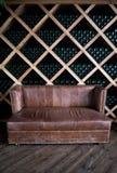 Garrafas do vinho em uma adega de vinho Sofá marrom velho do vintage Fotos de Stock Royalty Free