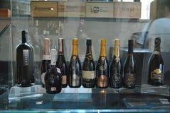 Garrafas do vinho em uma janela da loja Fotos de Stock Royalty Free