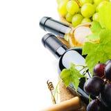 Garrafas do vinho vermelho e branco com uva fresca Fotos de Stock Royalty Free