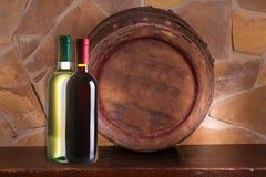 Garrafas do vinho vermelho e branco, tambor de vinho velho na adega Imagem de Stock