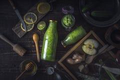 Garrafas e frasco com batido verde e os ingredientes diferentes na bandeja de madeira horizontal Fotografia de Stock Royalty Free