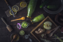 Garrafas e frasco com batido verde e os ingredientes diferentes na opinião superior da bandeja de madeira Fotografia de Stock Royalty Free