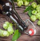 Garrafas e lúpulo vazios de cerveja na tabela de madeira Imagem de Stock