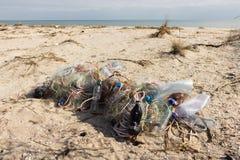 Garrafas e redes de pesca plásticas vazias na areia Lixo na praia Costa de mar suja Poluição ambiental fotografia de stock