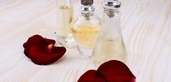 Garrafas e rosas fêmeas bonitas de perfume Imagens de Stock Royalty Free