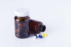 Garrafas e tabuletas da medicina no fundo branco Fotografia de Stock Royalty Free