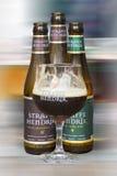 Garrafas e vidro de cervejas de Bélgica Straffe Hendrik isolados no fundo borrado Imagens de Stock Royalty Free