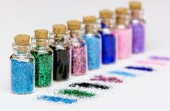 Garrafas pequenas com sparkles coloridos e as lantejoulas dispersadas no fundo branco foto de stock royalty free