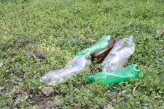 Garrafas plásticas esmagadas da água mineral na grama, o conceito da proteção ambiental, obstrução do ambiente foto de stock
