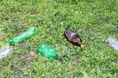 Garrafas plásticas esmagadas da água mineral na grama, o conceito da proteção ambiental, obstrução do ambiente fotos de stock royalty free