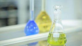 Garrafas químicas com líquido verde e azul no fundo branco Tubos de ensaio com o reagente químico colorido Laboratório Imagem de Stock