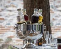 Garrafas refrigerando com álcool no grupo da tabela para o jantar O refrigerador reflete tabelas e cadeiras imagem de stock